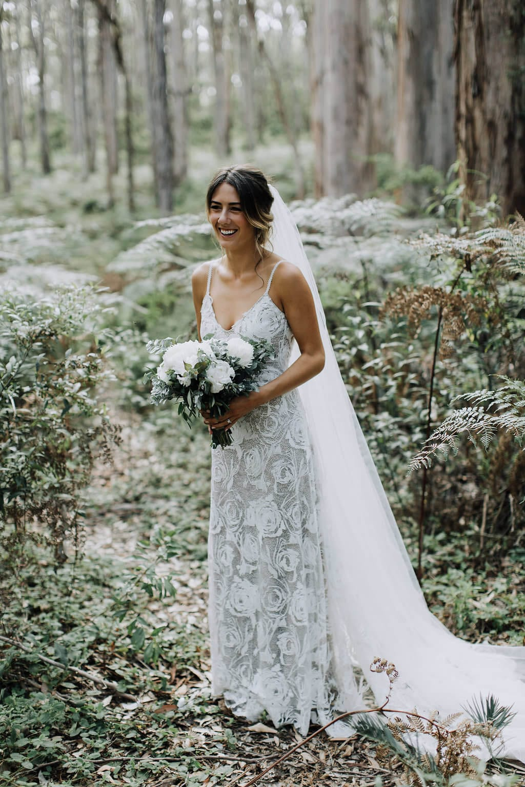 Bride wearing Grace Loves Lace Rosa Gown holding bouquet in forest