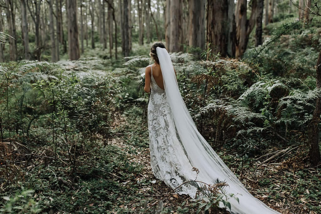 Back shot of bride wearing Grace Loves Lace Rosa Gown holding bouquet in forest