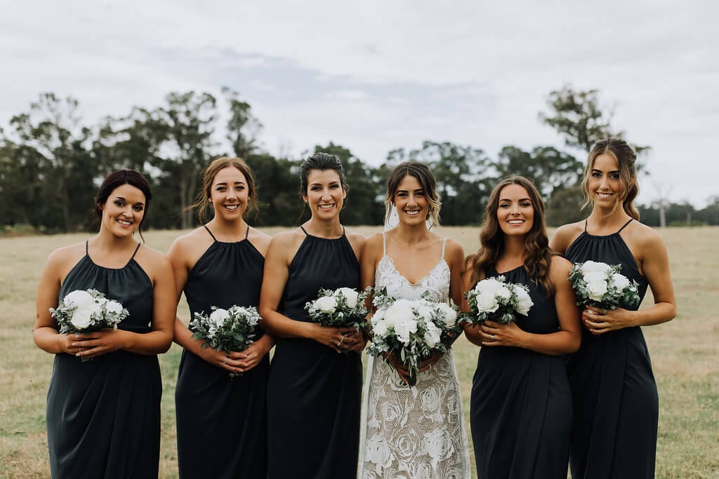 Bride wearing Grace Loves Lace Rosa Gown with bridesmaids holding bouquets