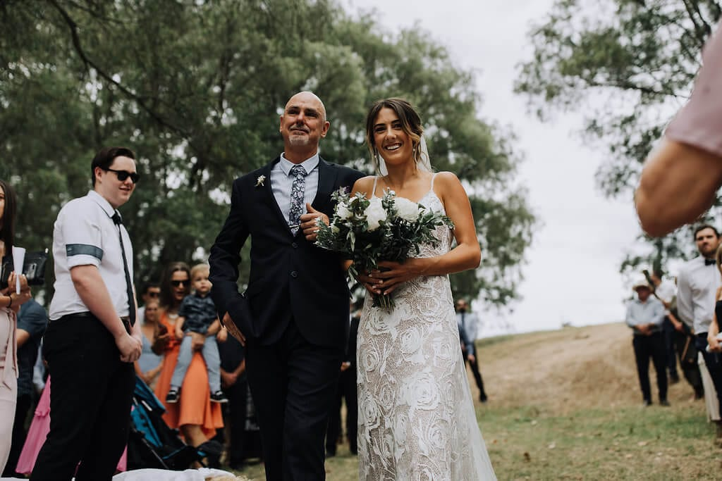 Bride wearing Grace Loves Lace Rosa Gown walking with father holding bouquet