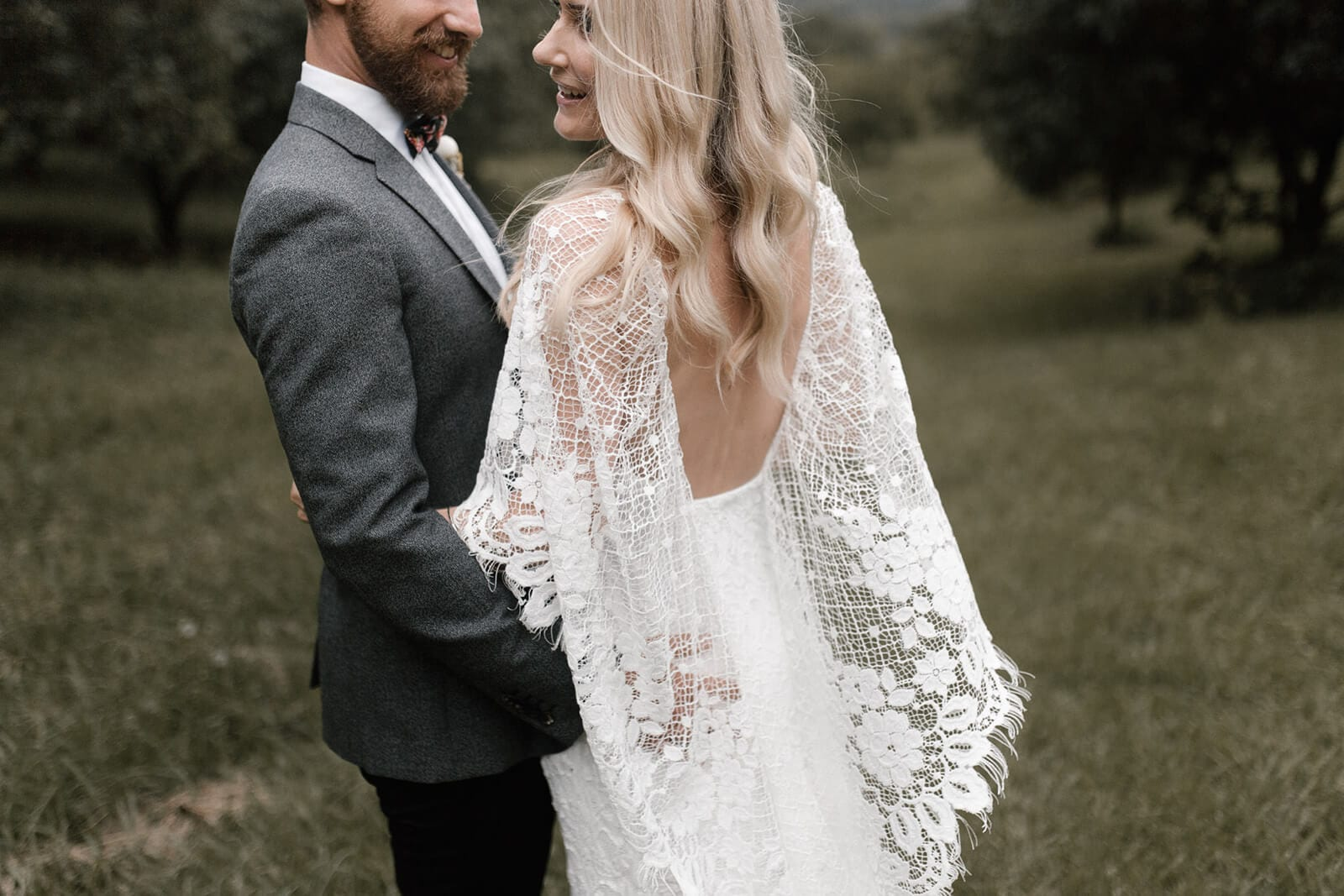 Back shot of bride wearing Grace Loves Lace Verdelle 2.0 Gown being held by groom