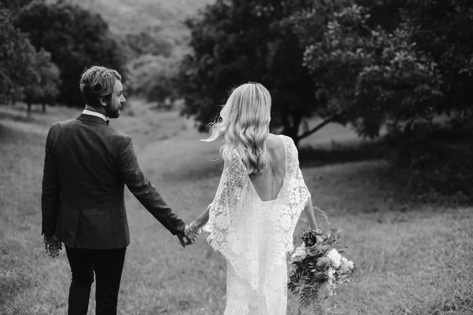 Black and white shot of bride wearing Grace Loves Lace Verdelle 2.0 Gown holding hands with groom