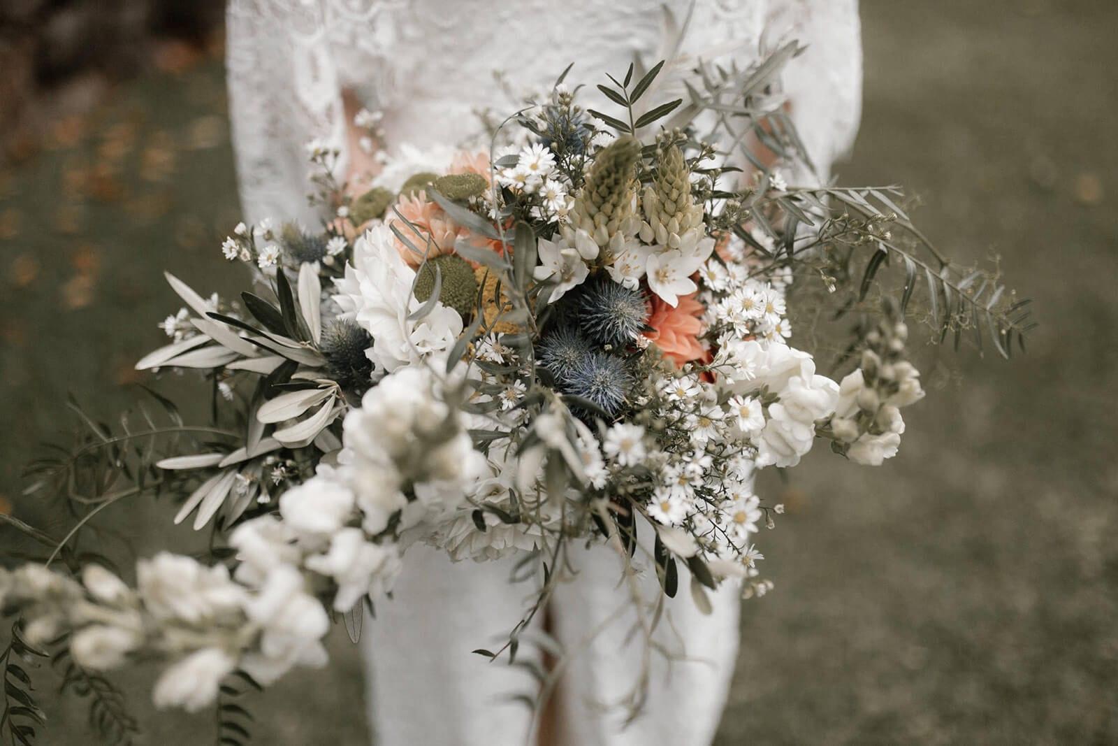 Close-up shot of bride wearing Grace Loves Lace Verdelle 2.0 Gown holding bouquet