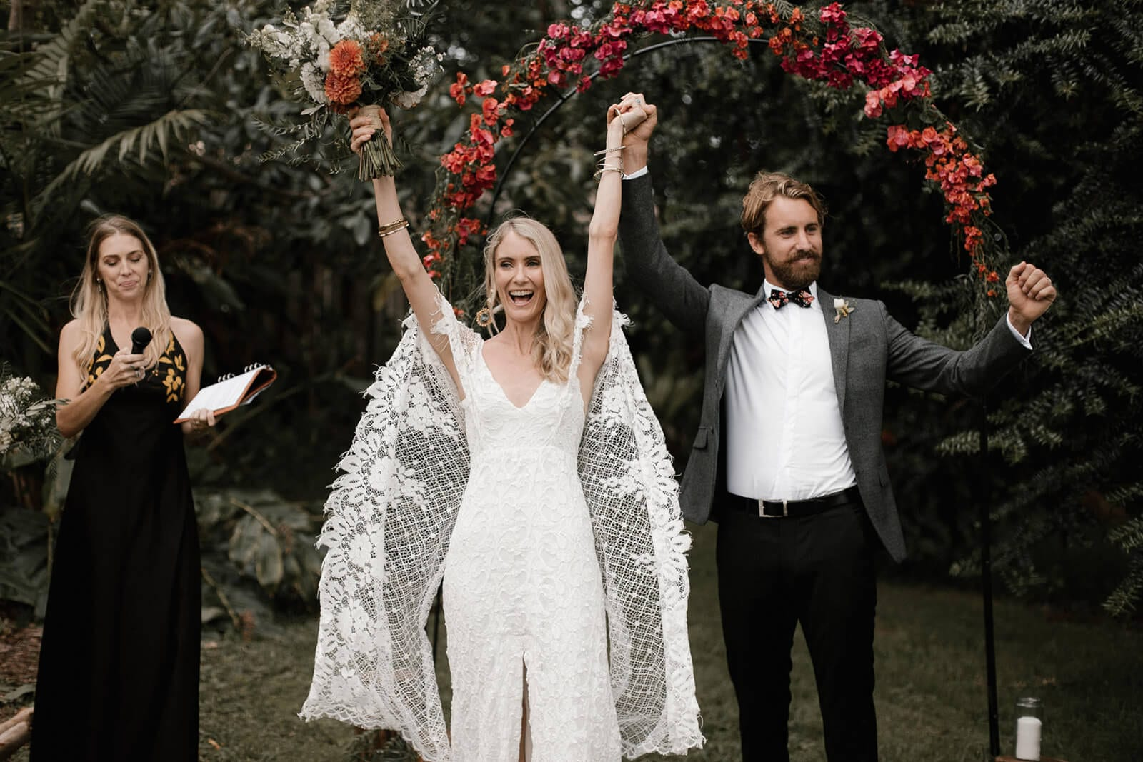 Bride wearing Grace Loves Lace Verdelle 2.0 Gown holding hands up with groom