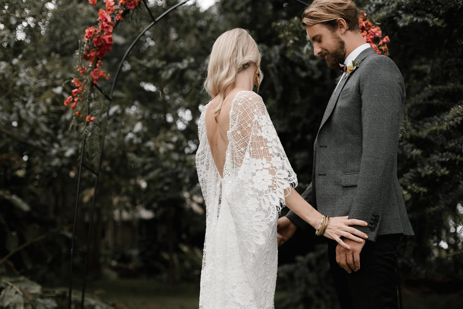 Bride wearing Grace Loves Lace Verdelle 2.0 Gown holding hands with groom