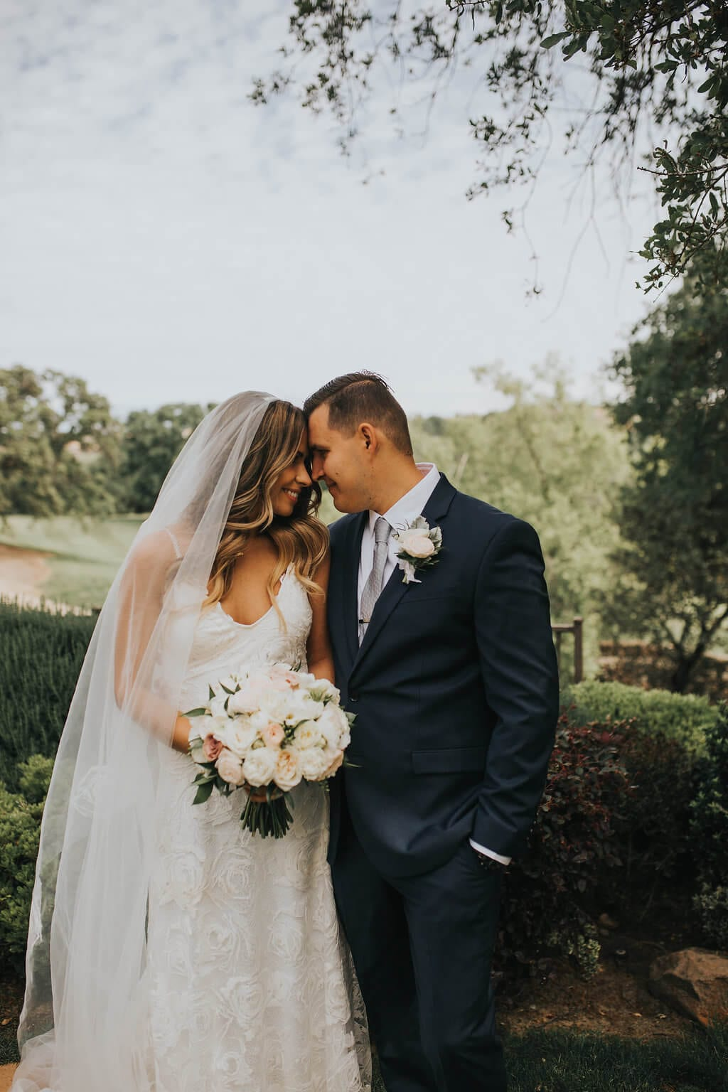 Bride wearing Grace Loves Lace Rosa Gown holding bouquet with groom