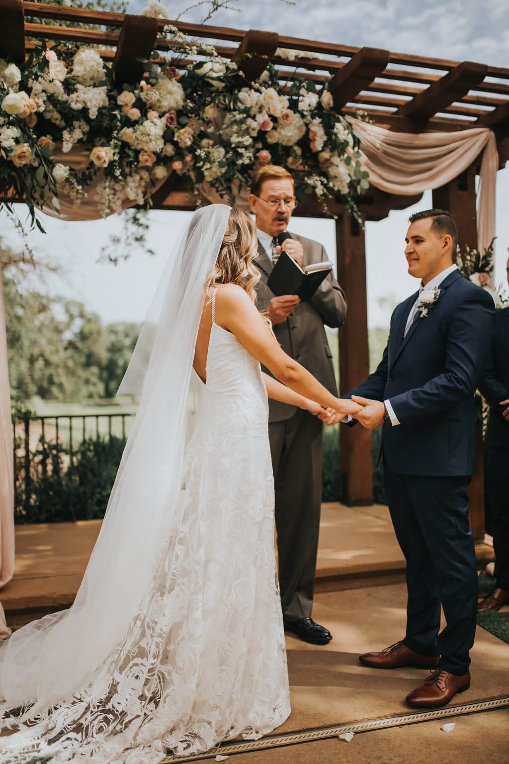 Bride wearing Grace Loves Lace Rosa Gown holding hands with groom during ceremony