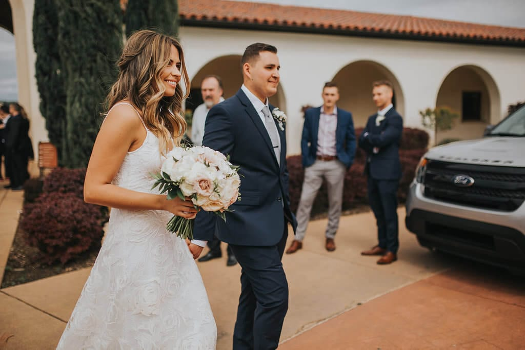 Bride wearing Grace Loves Lace Rosa Gown holding bouquet walking with groom