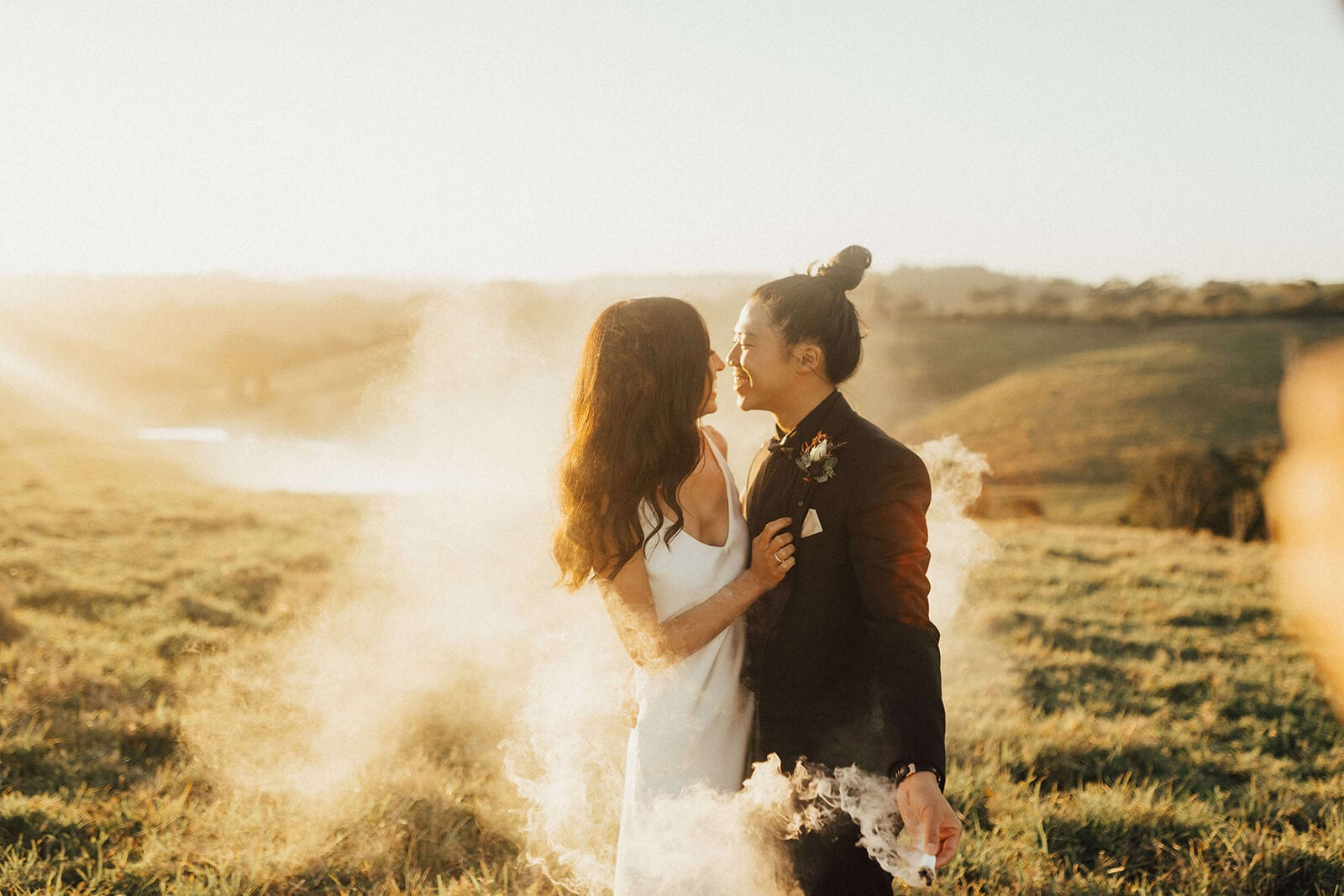 Brunette bride wearing Grace Loves Lace Arlo Gown embracing groom in smokey field