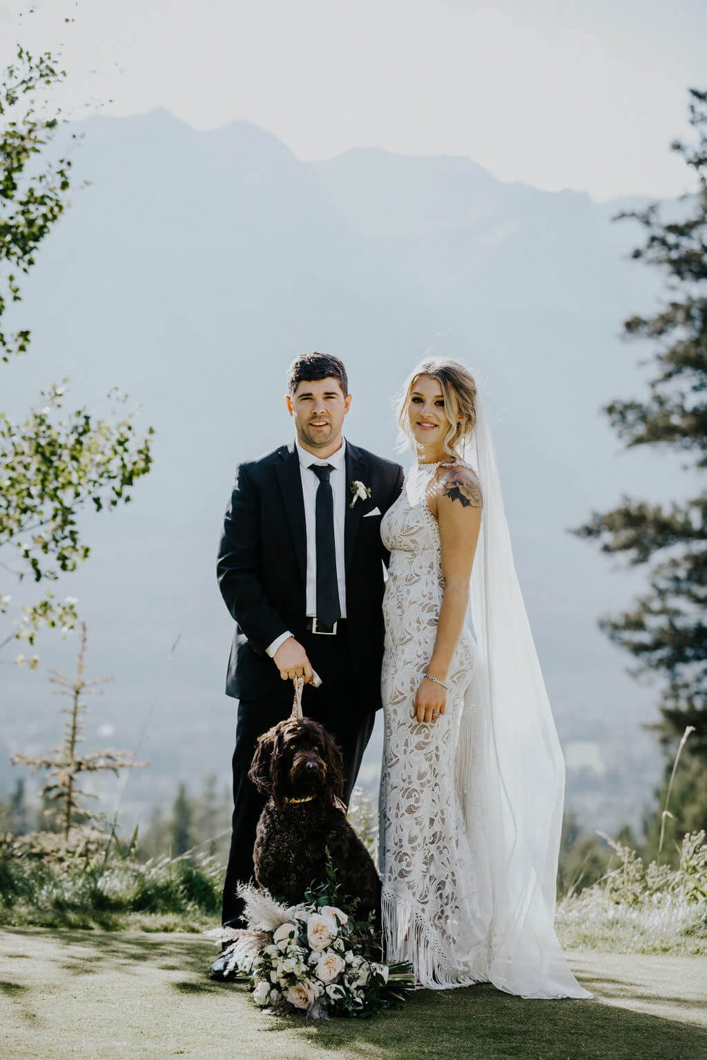 Blonde bride wearing Grace Loves Lace Edie Gown standing with groom and black dog