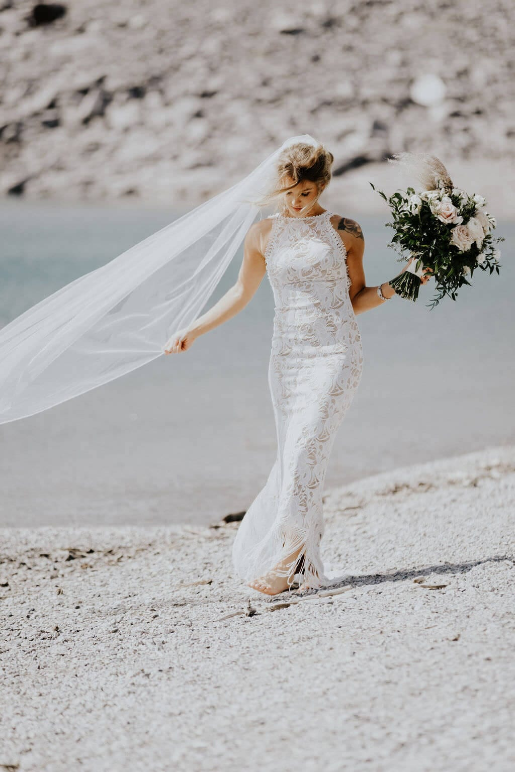 Blonde bride wearing Grace Loves Lace Edie Gown holding bouquet with veil blowing in the wind