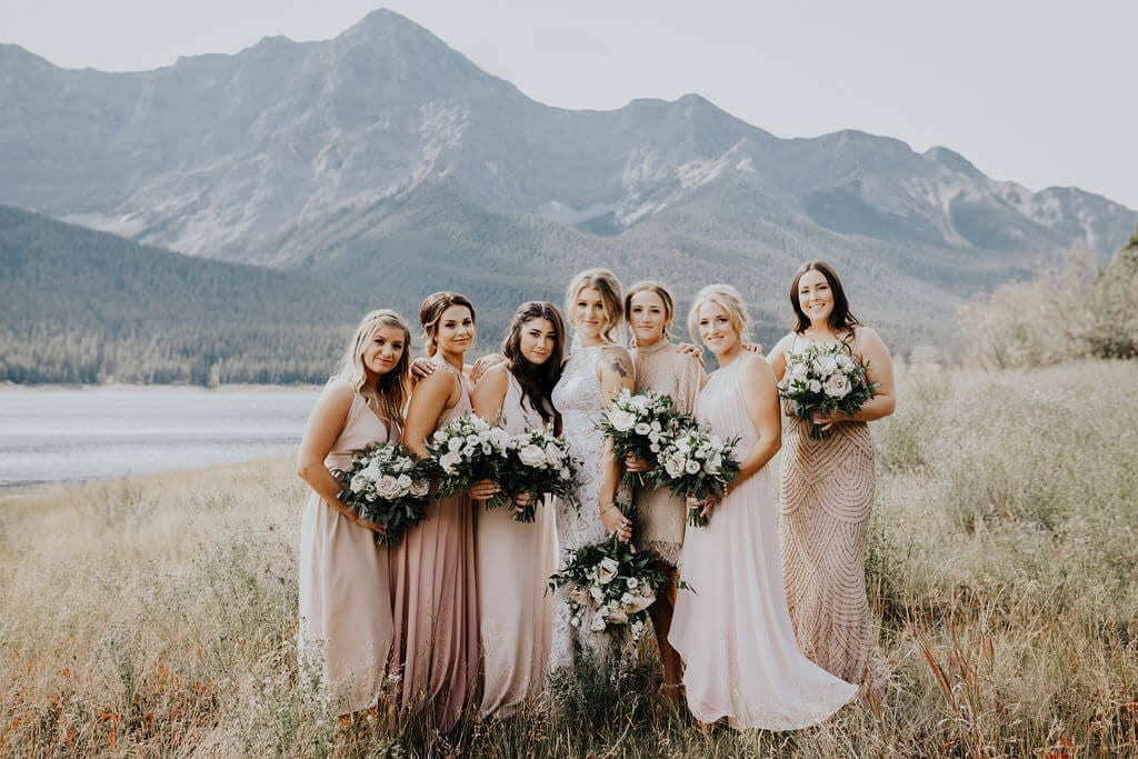 Blonde bride wearing Grace Loves Lace Edie Gown with bridesmaids holding bouquets