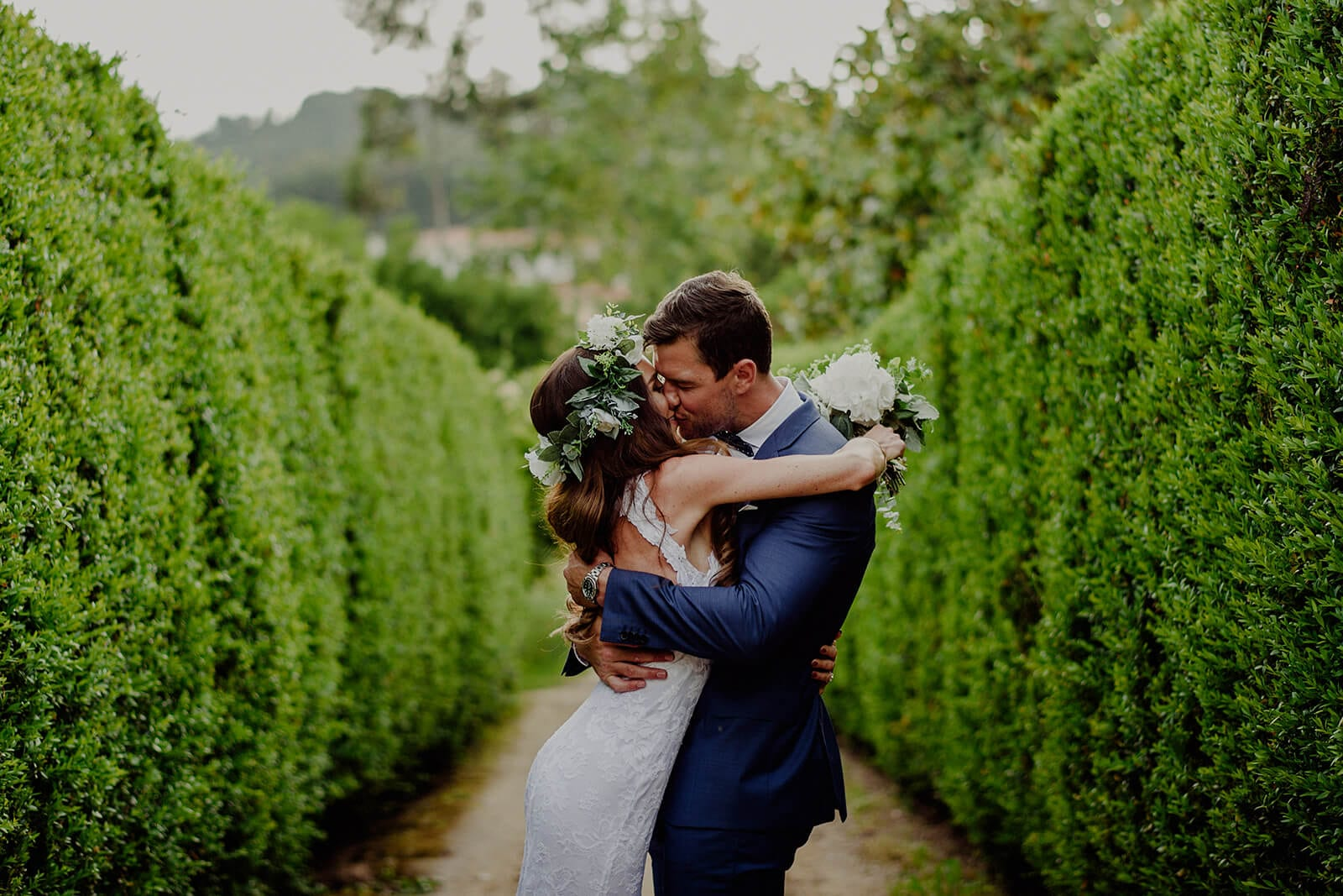 Bride wearing Grace Loves Lace Alexandra Gown kissing groom holding bouquet