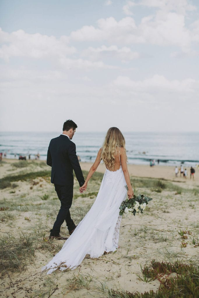 Bride wearing Grace Loves Lace Inca Gown holding hands with groom on beach