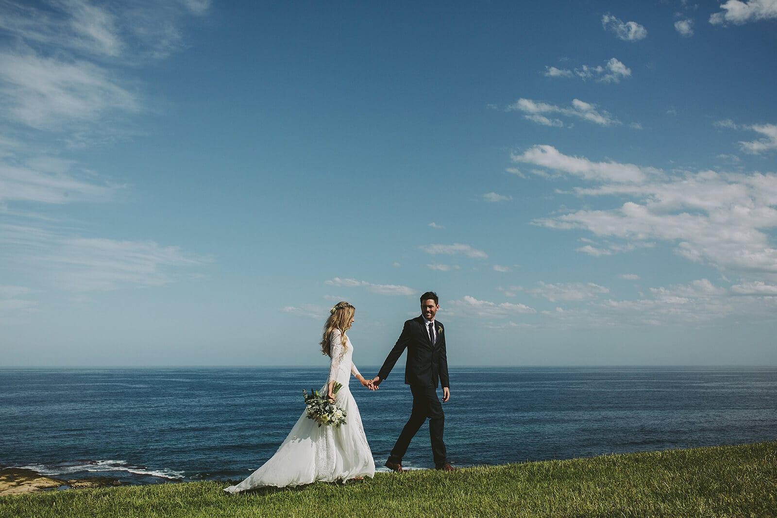 Bride wearing Grace Loves Lace Inca Gown being held by groom on seaside