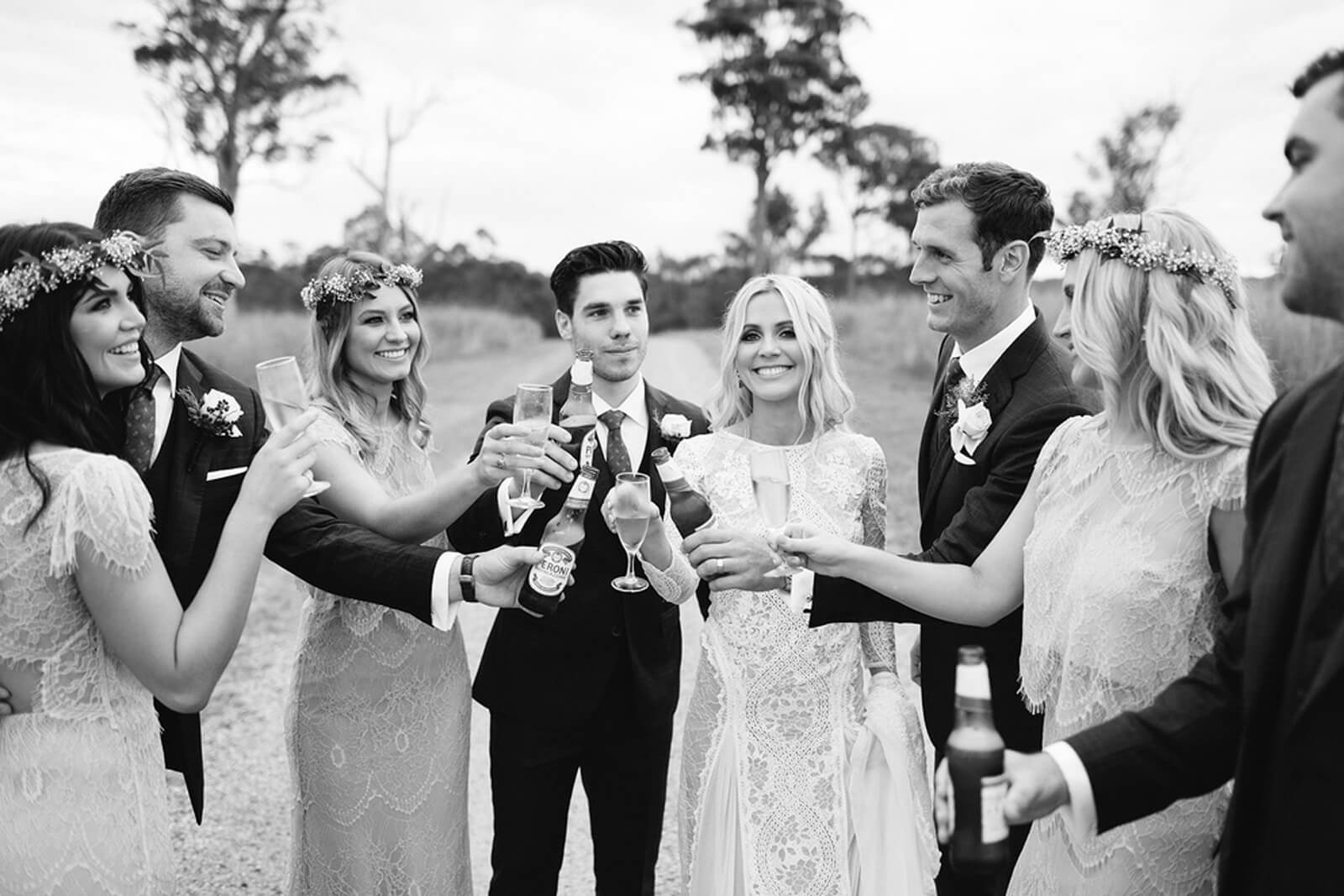 Black and white shot of bride wearing Grace Loves Lace Inca Gown walking with wedding party drinking champagne