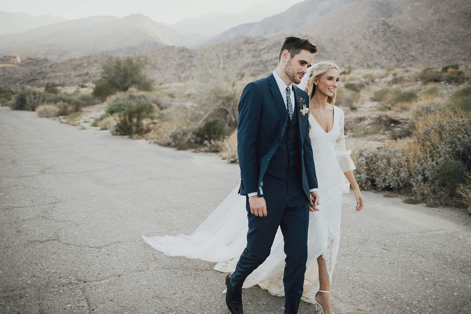 Blonde bride wearing Grace Loves Lace Francis Gown walking with groom