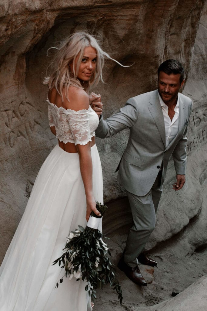 Blonde bride wearing Grace Loves Lace Luna Gown holding bouquet holding hands with groom in sandy cave path