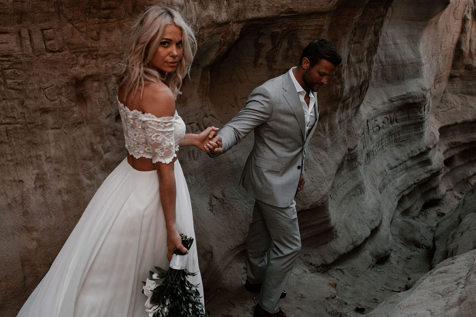 Blonde bride wearing Grace Loves Lace Luna Gown following groom down sandy cavern holding bouquet