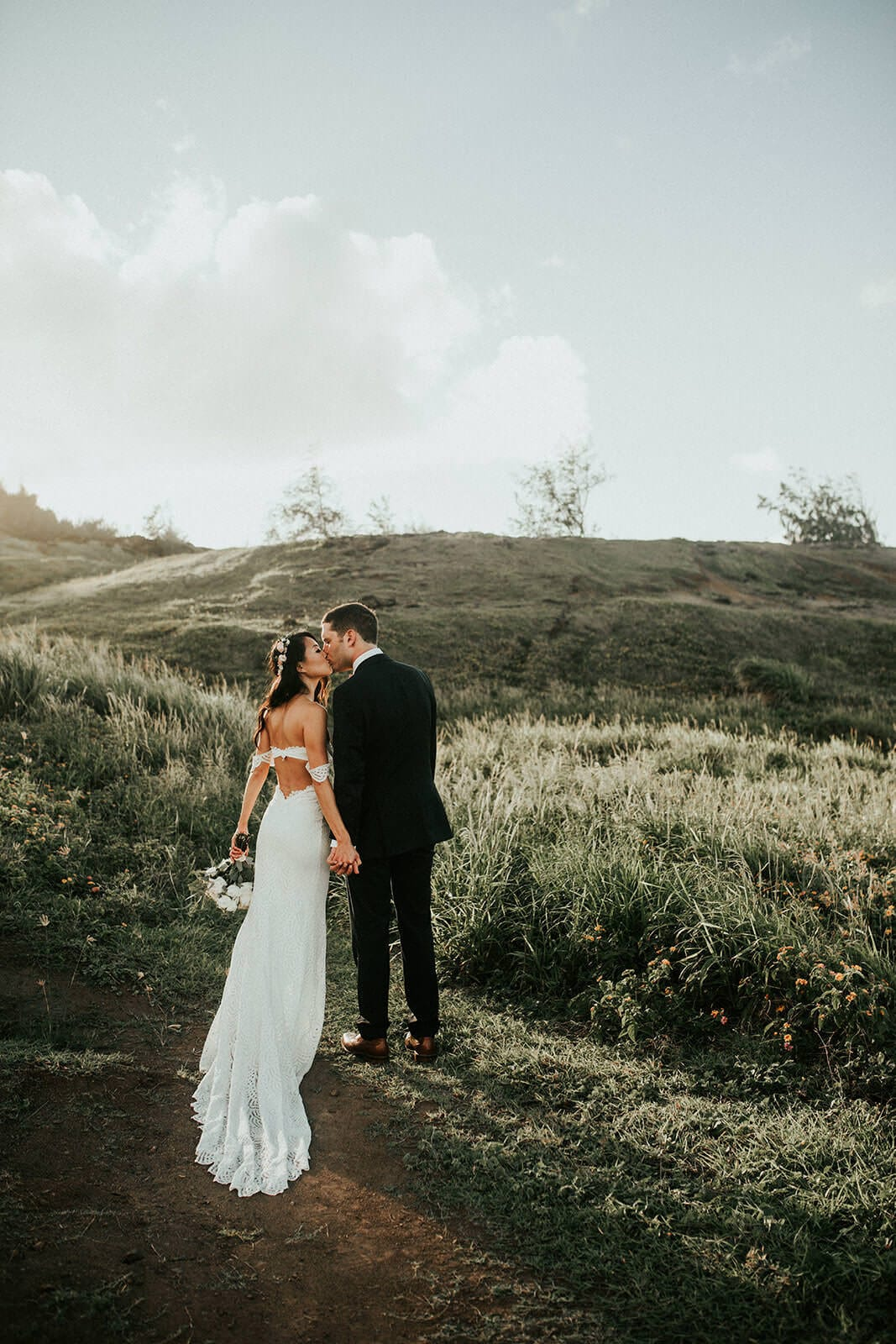 Brunette bride wearing Grace Loves Lace Paloma Gown kissing groom on green grassy hill