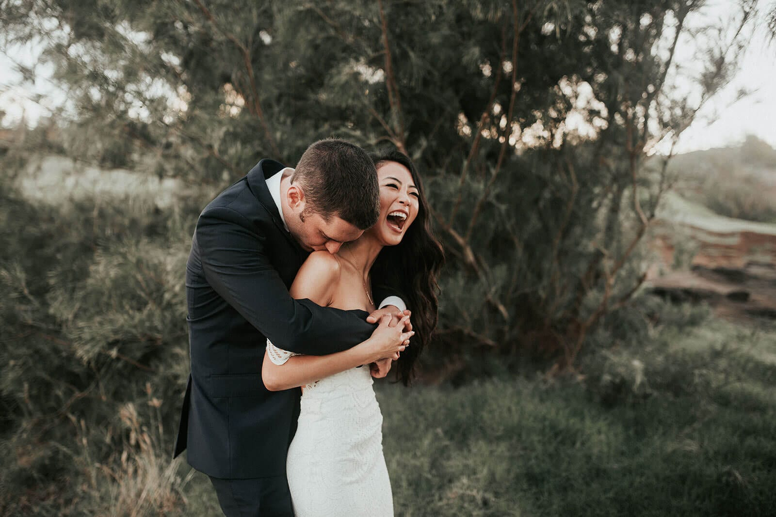 Brunette bride wearing Grace Loves Lace Paloma Gown being held by groom laughing