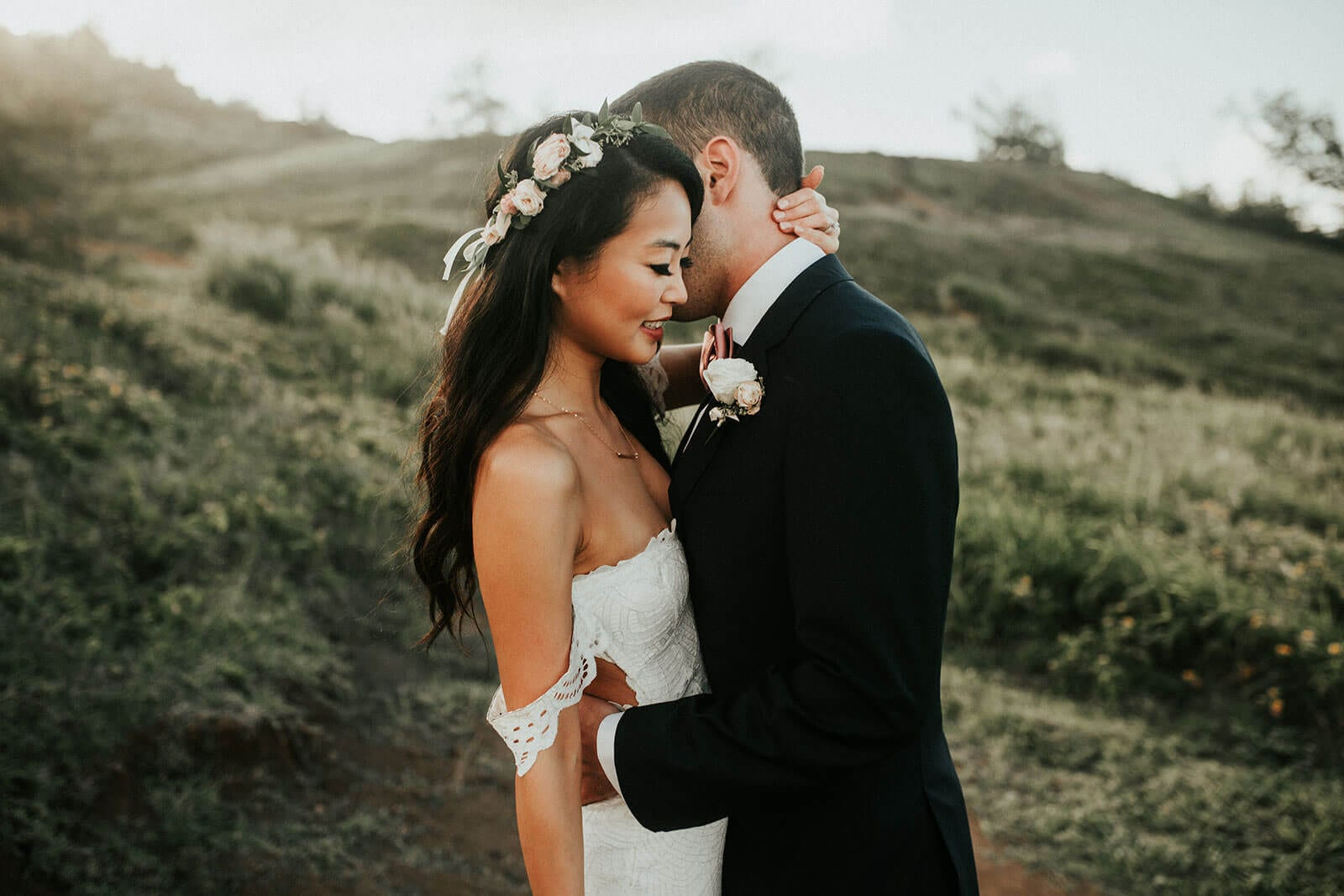 Brunette bride wearing Grace Loves Lace Paloma Gown embracing groom on grassy hill