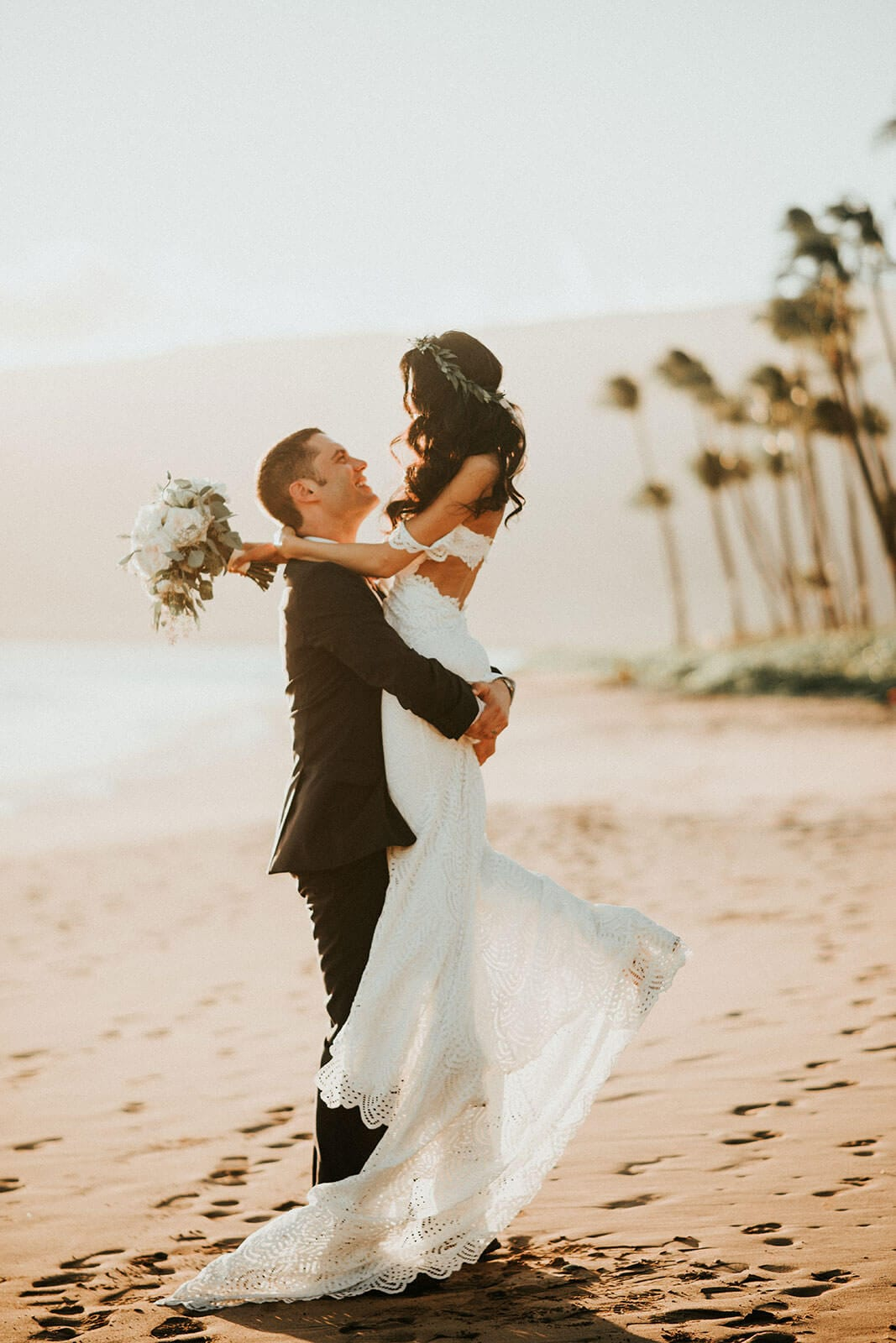 Brunette bride wearing Grace Loves Lace Paloma Gown being held by groom on beach holding bouquet