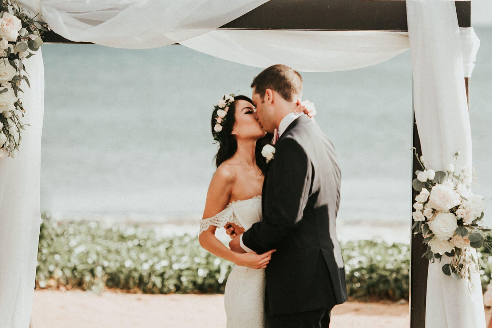 Brunette bride wearing Grace Loves Lace Paloma Gown kissing groom on beach