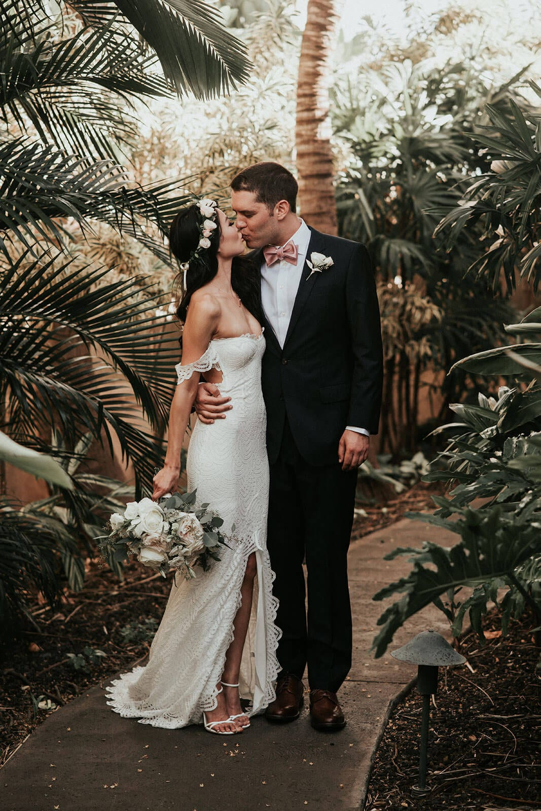 Brunette bride wearing Grace Loves Lace Paloma Gown kissing groom on garden path