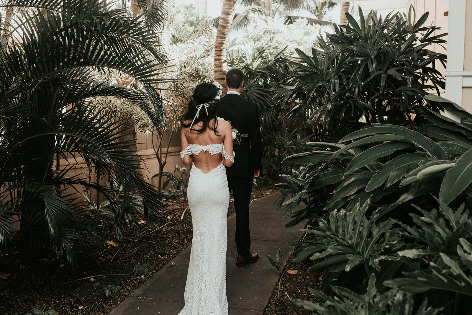 Back shot of bride wearing Grace Loves Lace Paloma Gown walking behind groom along garden path