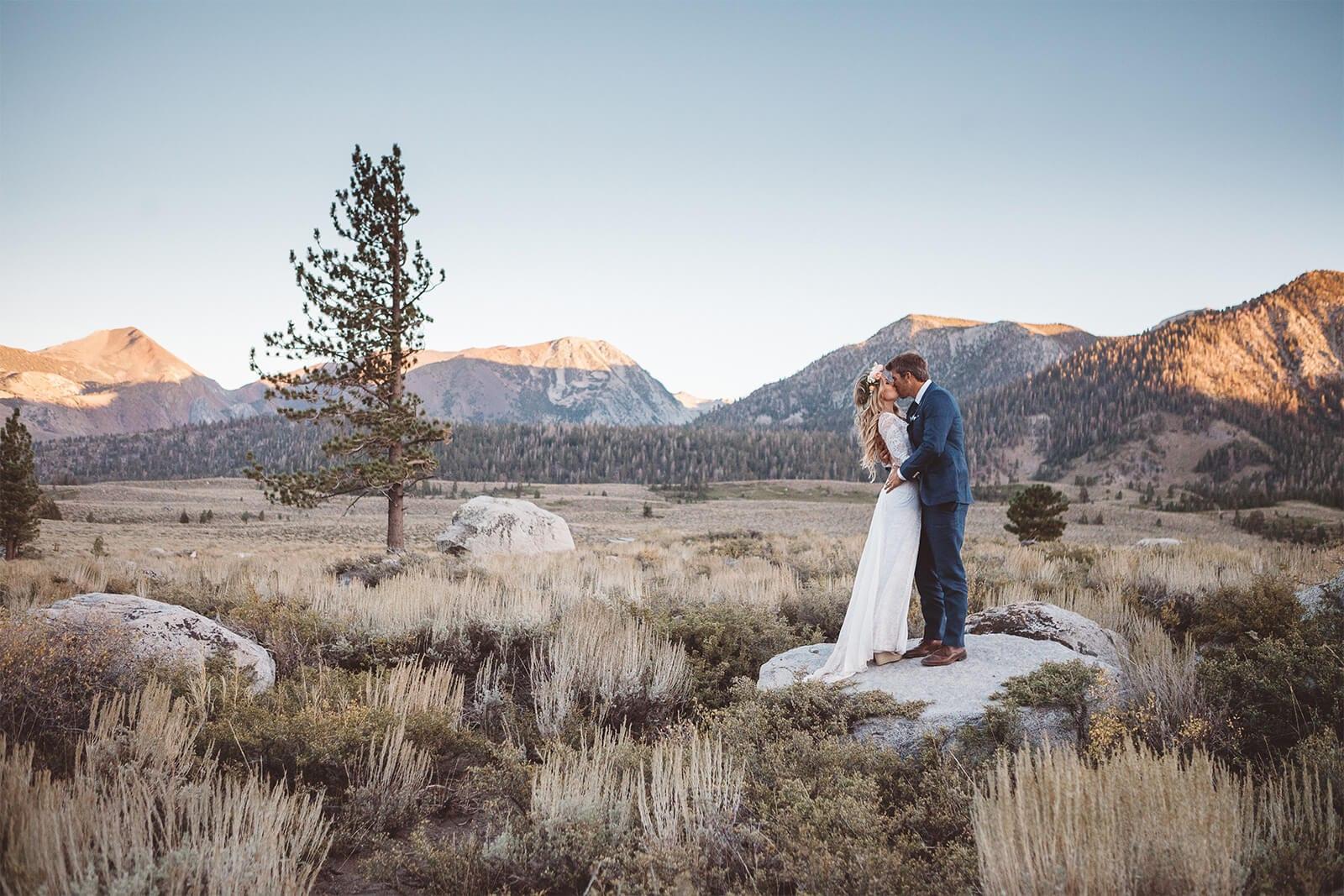 Bride wearing Grace Loves Lace Inca Gown kissing groom on rock
