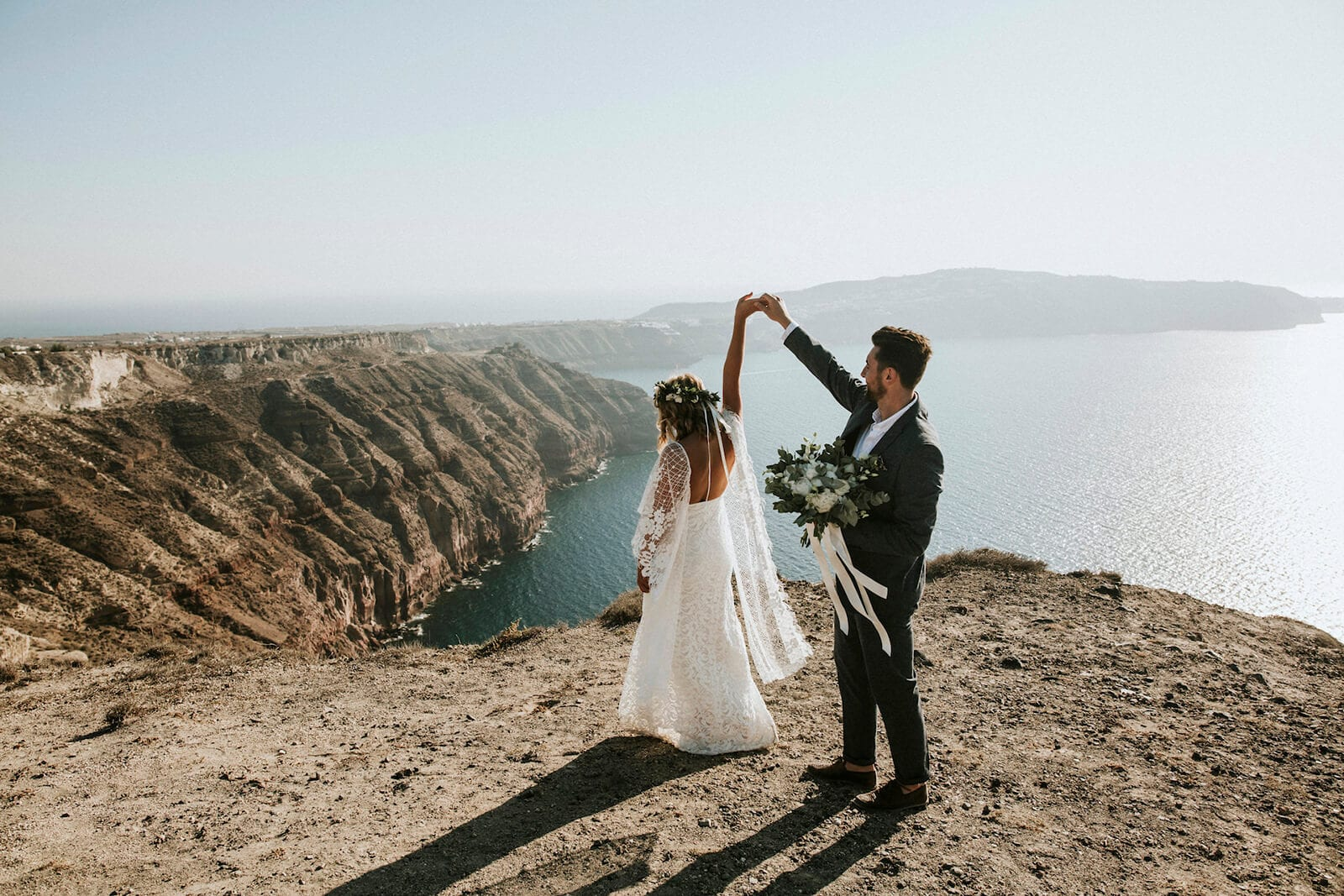 Bride wearing Grace Loves Lace Verdelle 2.0 Gown dancing with groom on seaside cliff