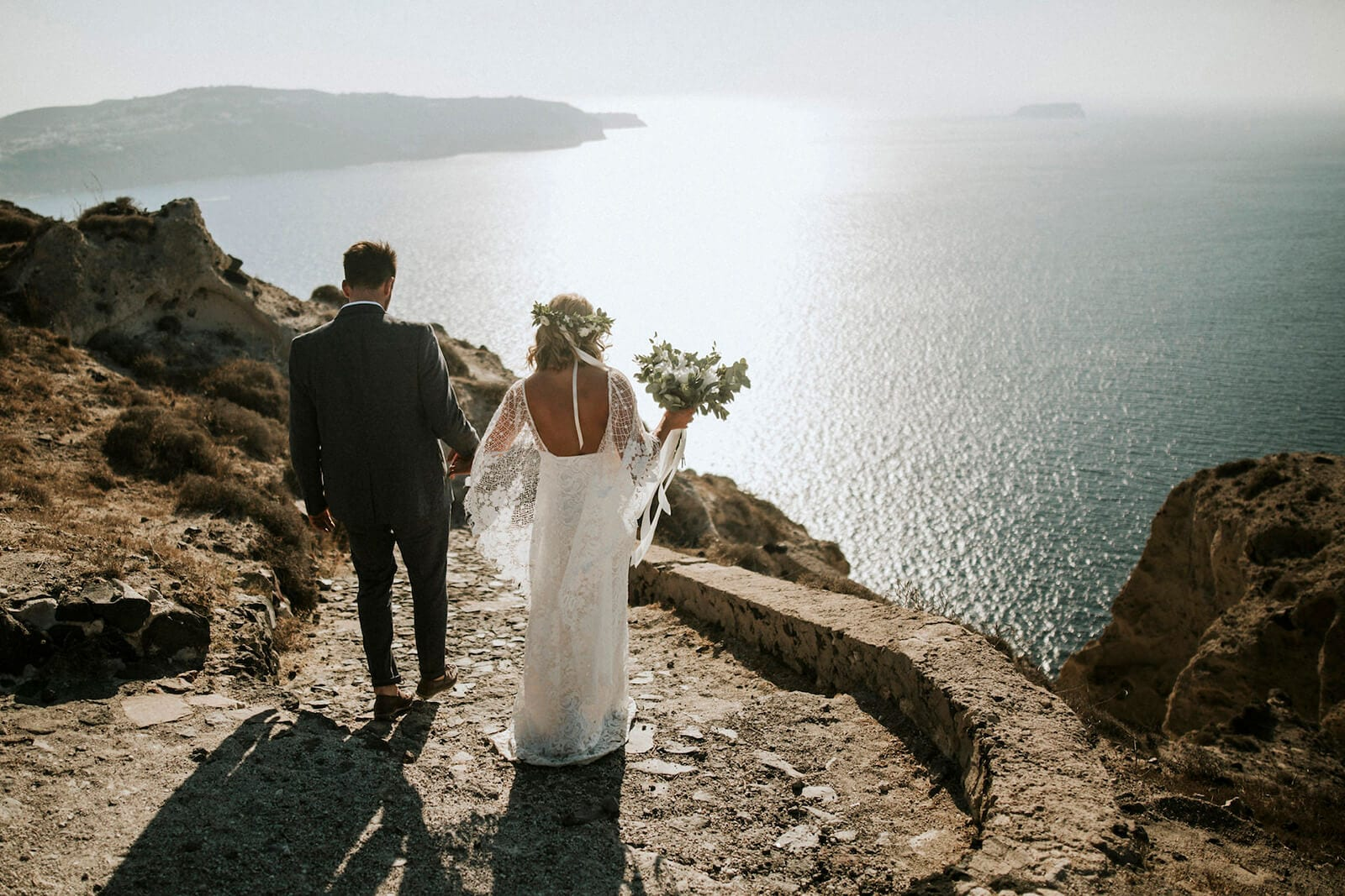 Bride wearing Grace Loves Lace Verdelle 2.0 Gown holding hands with groom on seaside cliff