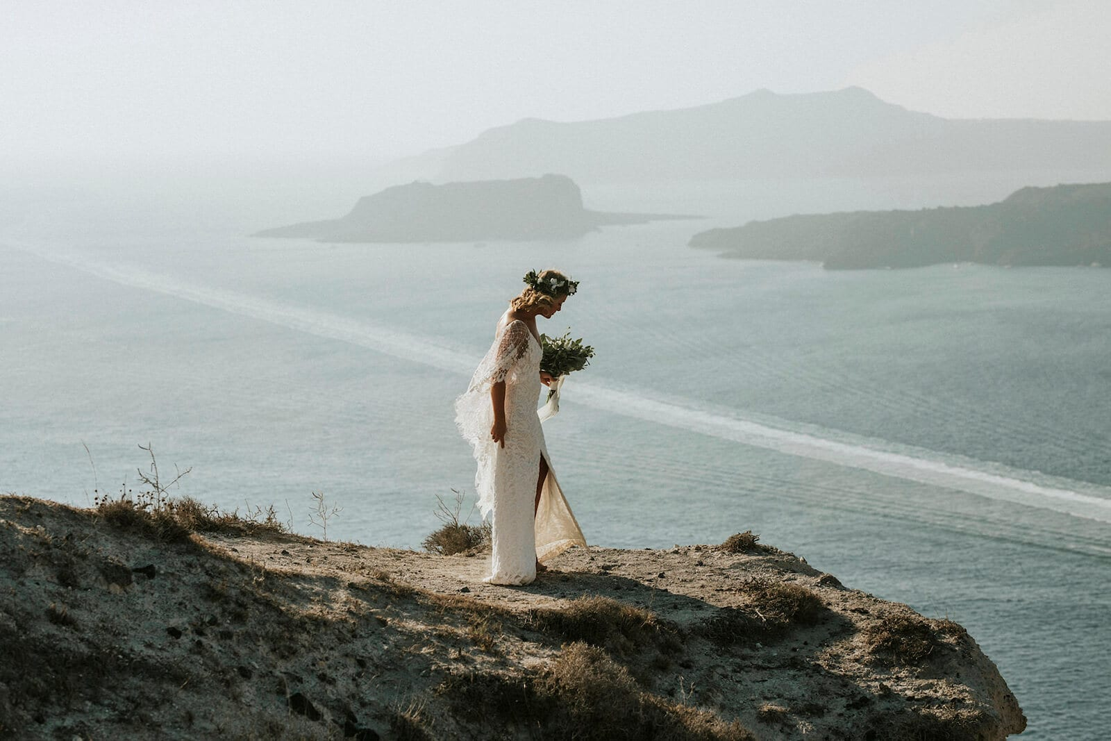 Bride wearing Grace Loves Lace Verdelle 2.0 Gown holding bouquet standing on seaside cliff