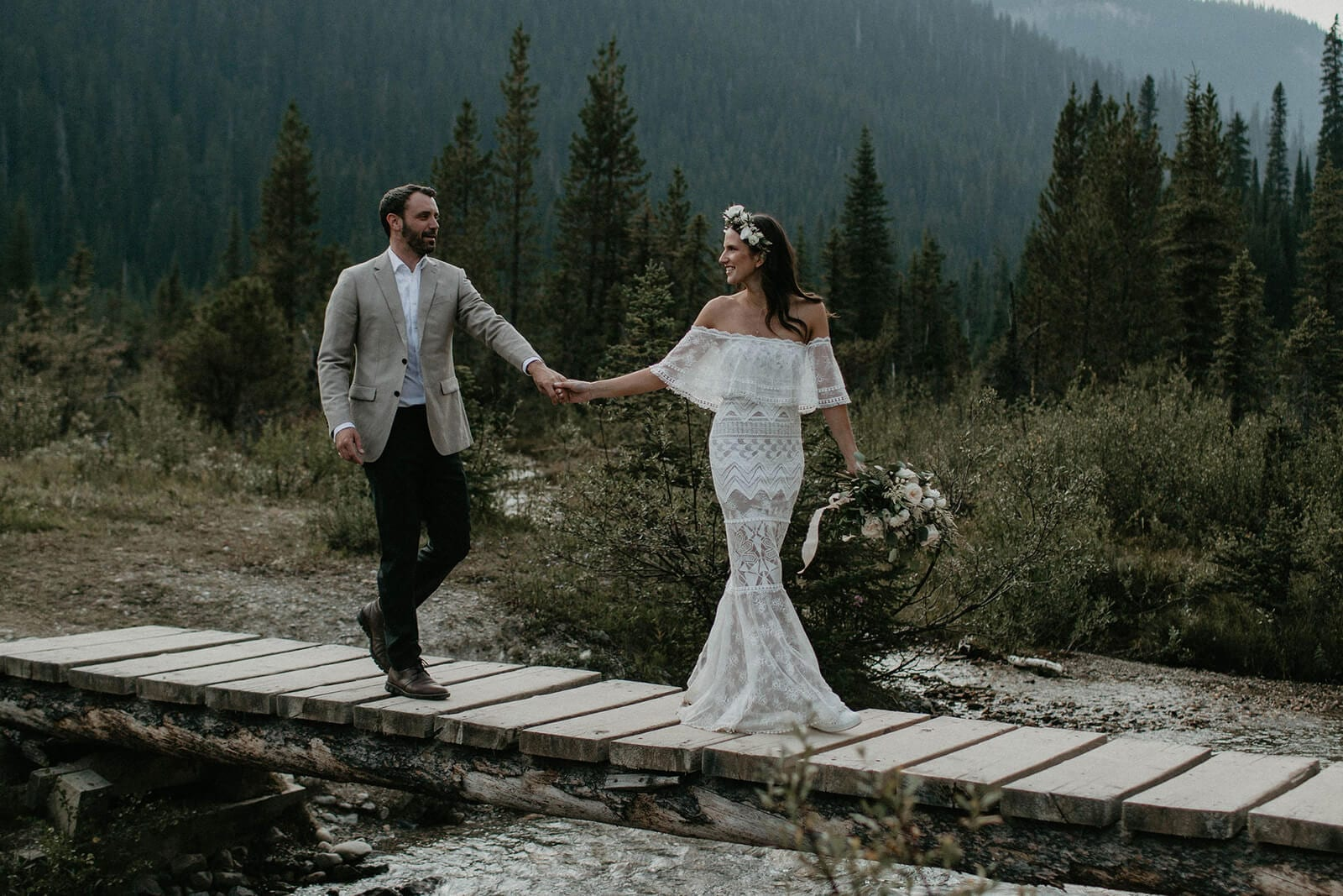 Brunette bride wearing Grace Loves Lace Emanuela Gown holding bouquet walking with groom on narrow bridge over water