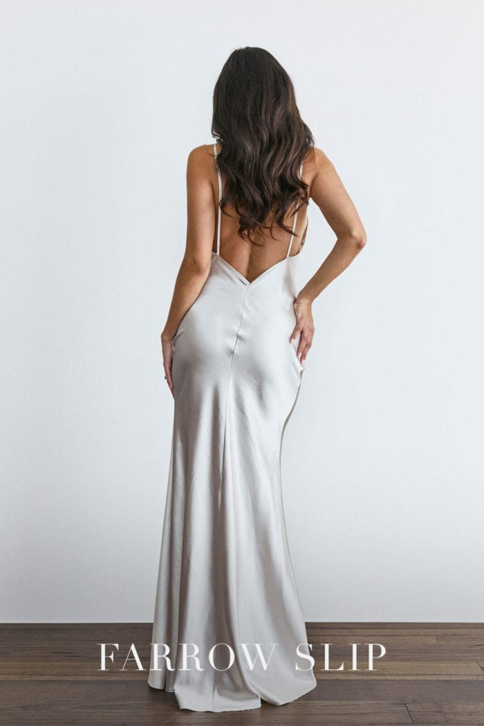 Back shot of bridesmaid wearing Grace Loves Lace Farrow Slip Gown with hands on buttocks