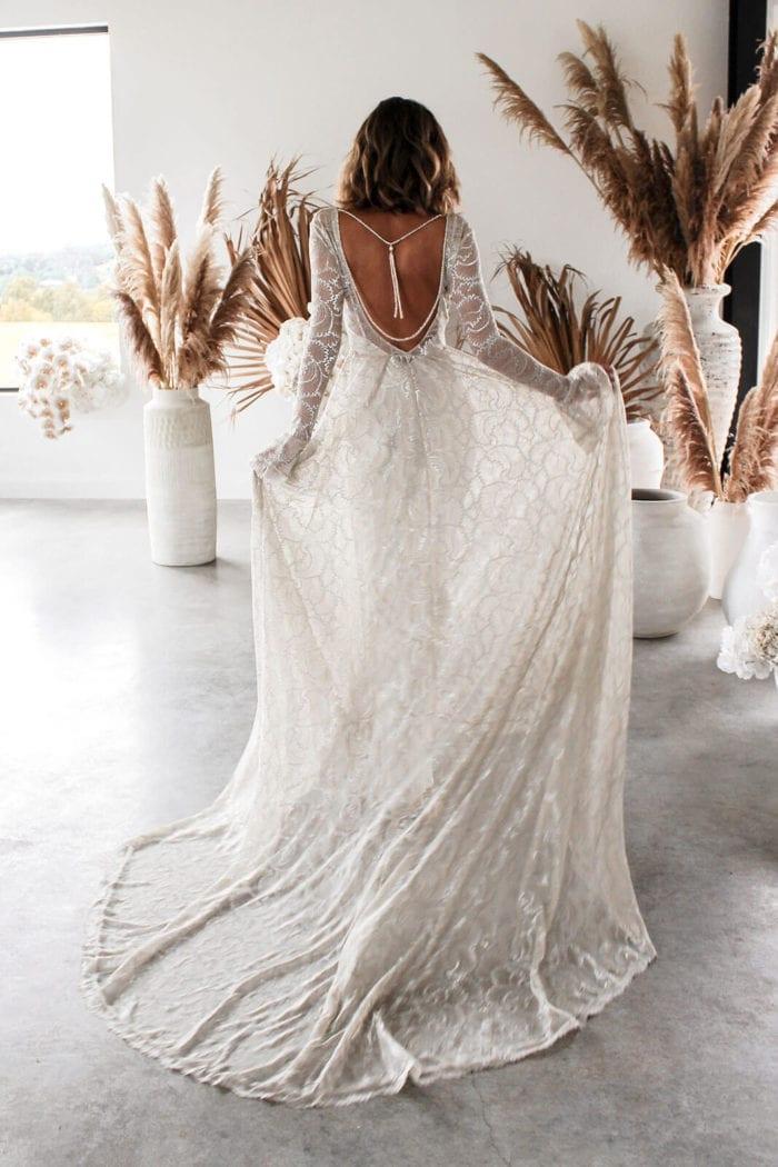Back shot of bride wearing Grace Loves Lace Mata Backpiece holding skirt on both hands