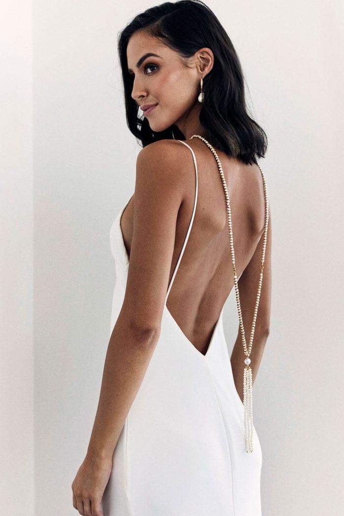 Back shot of bride wearing Grace Loves Lace Mata Backpiece looking over shoulder