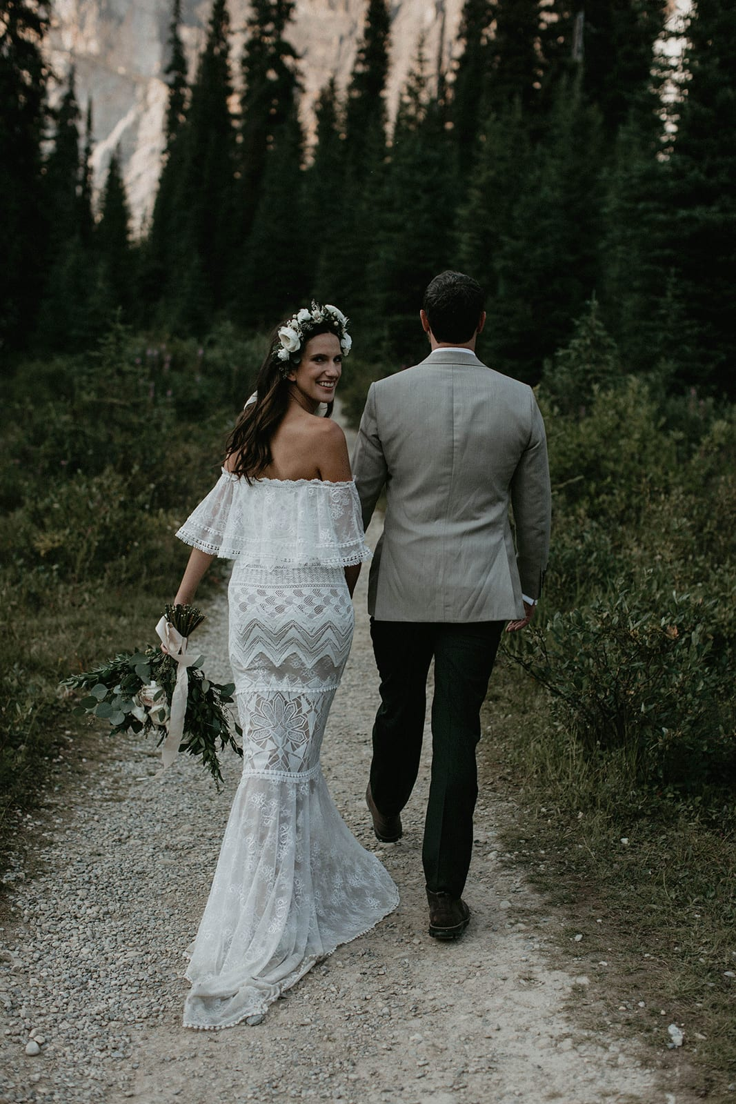 Back shot of bride wearing Grace Loves Lace Emanuela Gown holding bouquet walking with groom