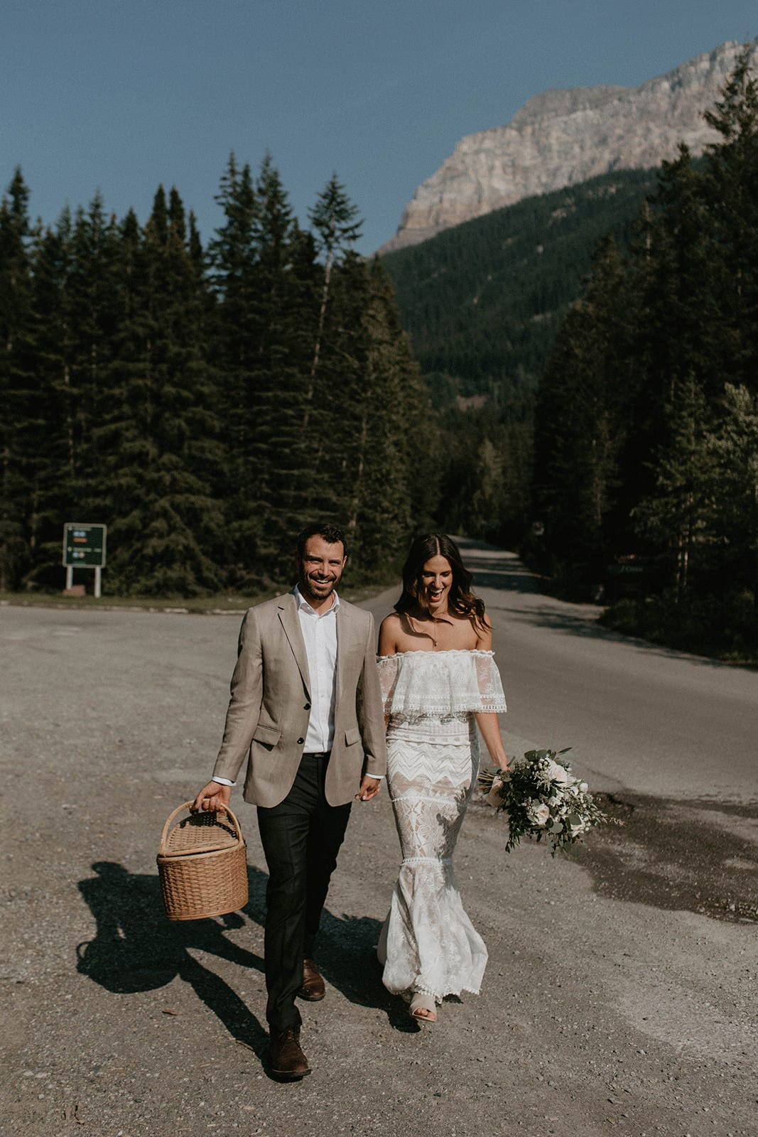 Brunette bride wearing Grace Loves Lace Emanuela Gown walking with groom down road