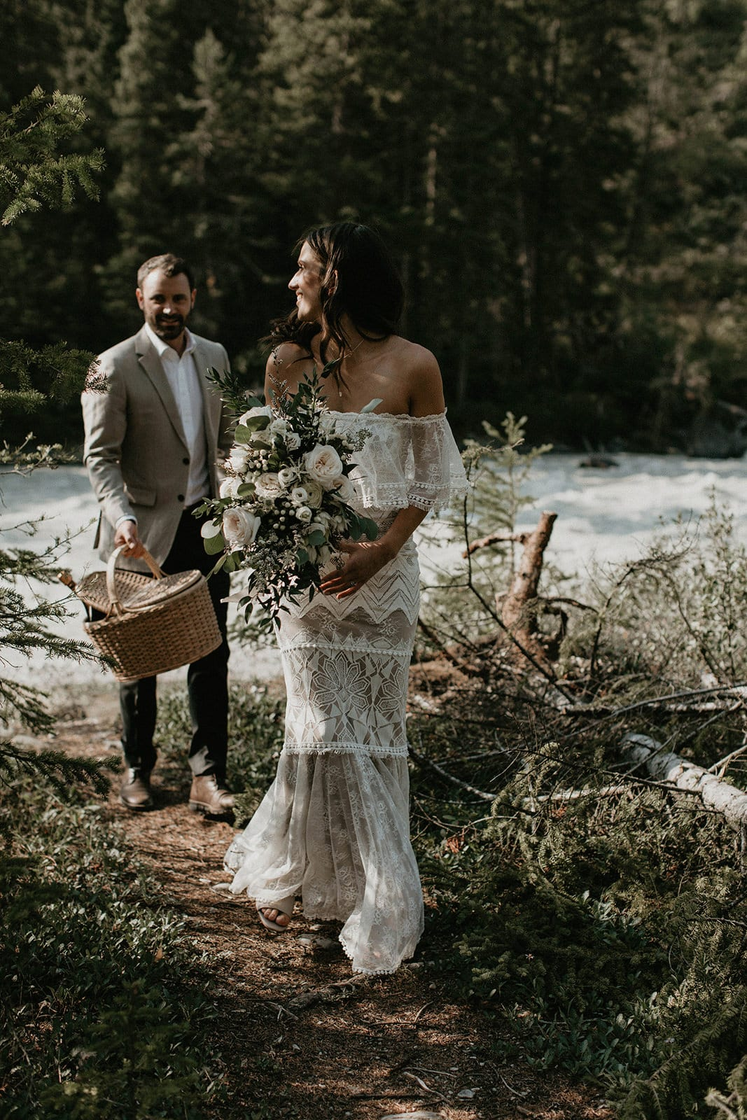 Brunette bride wearing Grace Loves Lace Emanuela Gown walking with groom through forest path beside river