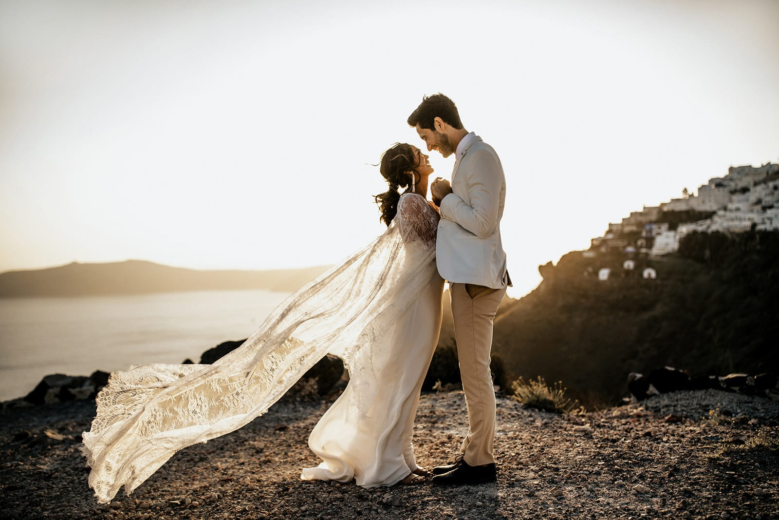 Brunette bride wearing Grace Loves Lace Arlo Gown holding hands with groom with dress blowing in wind