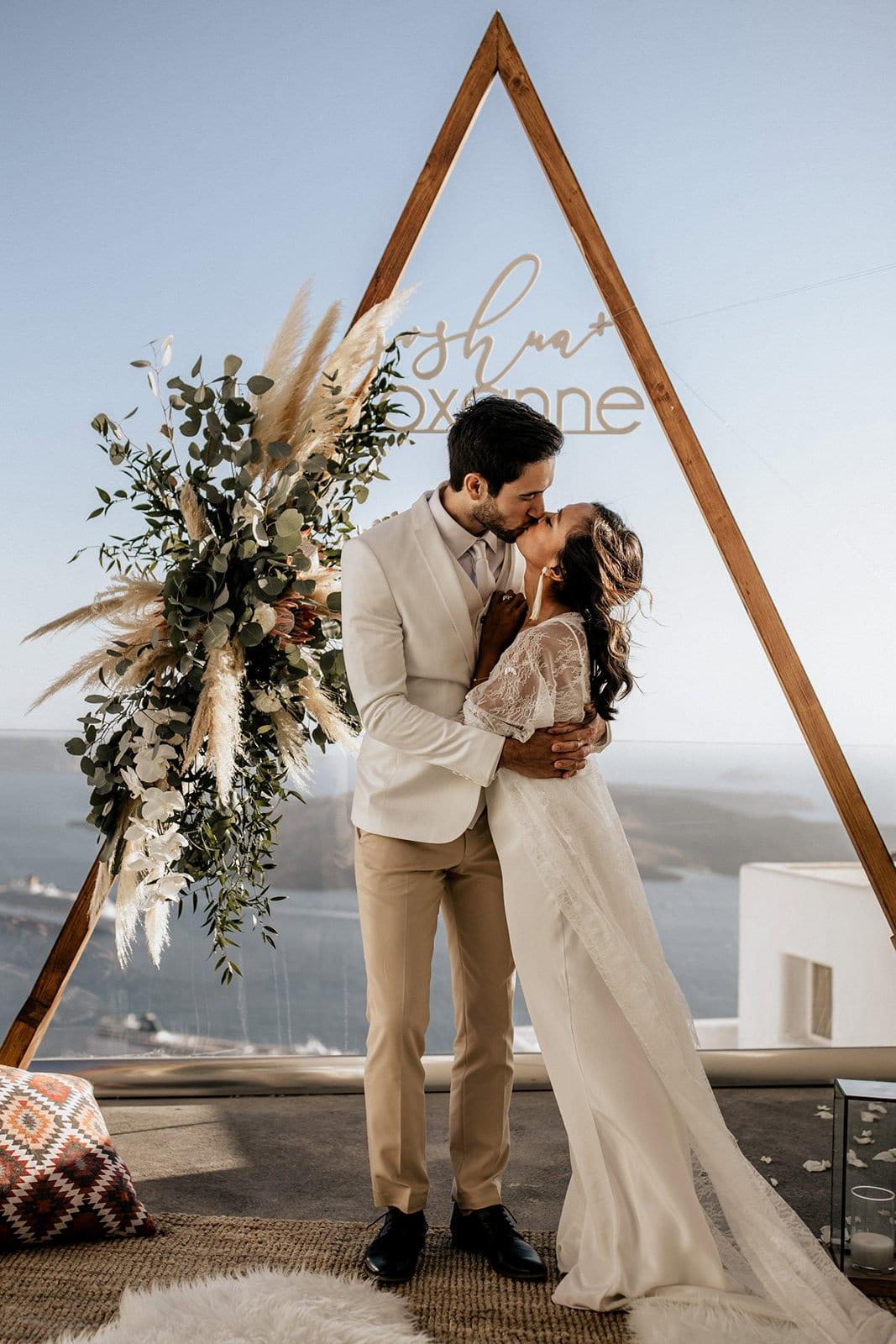 Brunette bride wearing Grace Loves Lace Arlo Gown kissing groom