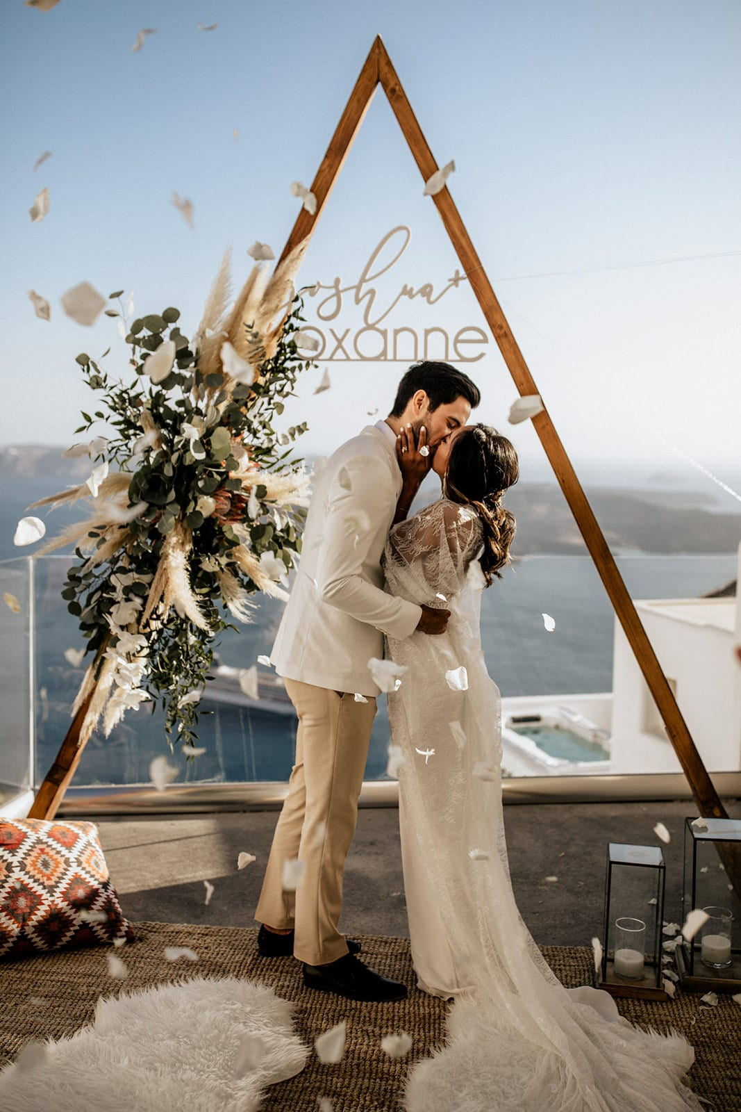 Brunette bride wearing Grace Loves Lace Arlo Gown kissing groom with white flower petal shower