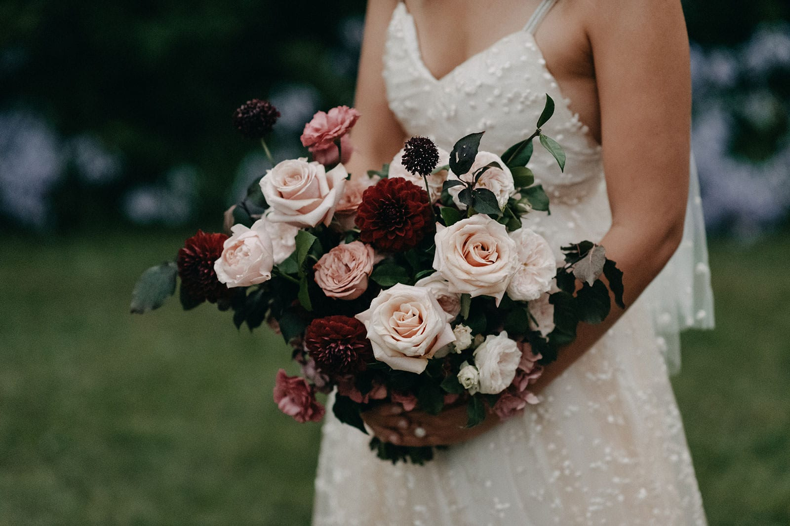 Close-up shot of bride wearing Grace Loves Lace Menha Gown holding bouquet