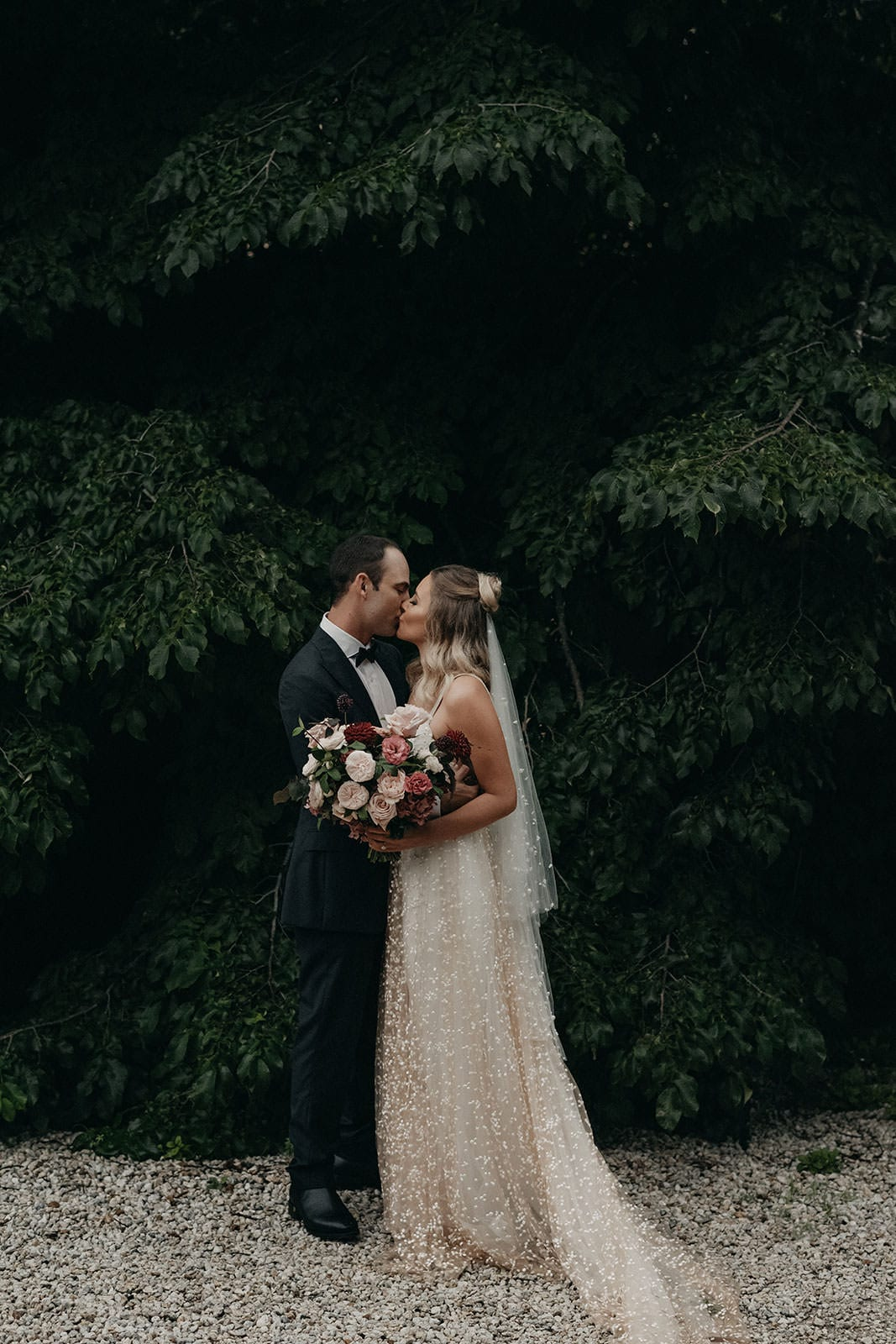 Blonde bride wearing Grace Loves Lace Menha Gown and matching veil kissing groom