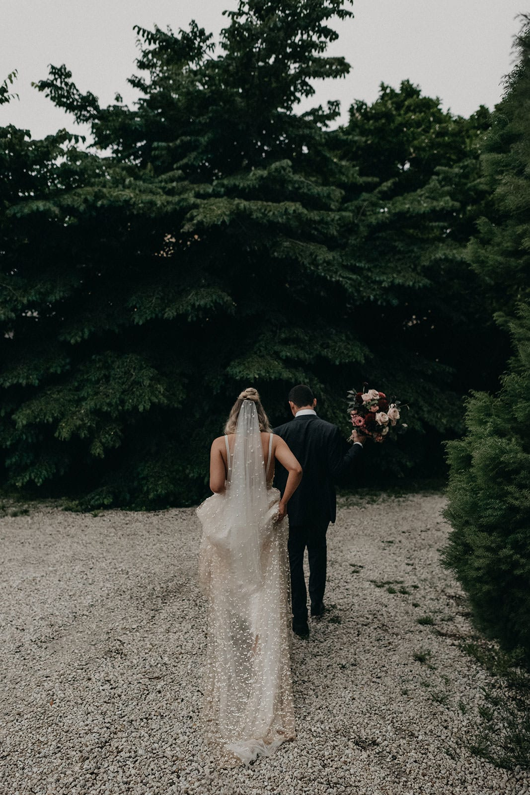 Blonde bride wearing Grace Loves Lace Menha Gown and matching veil walking with groom
