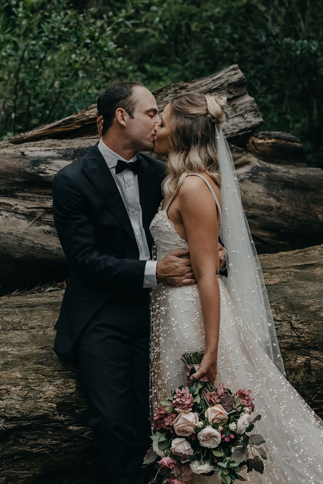 Blonde bride wearing Grace Loves Lace Menha Gown and matching veil kissing groom sitting on log