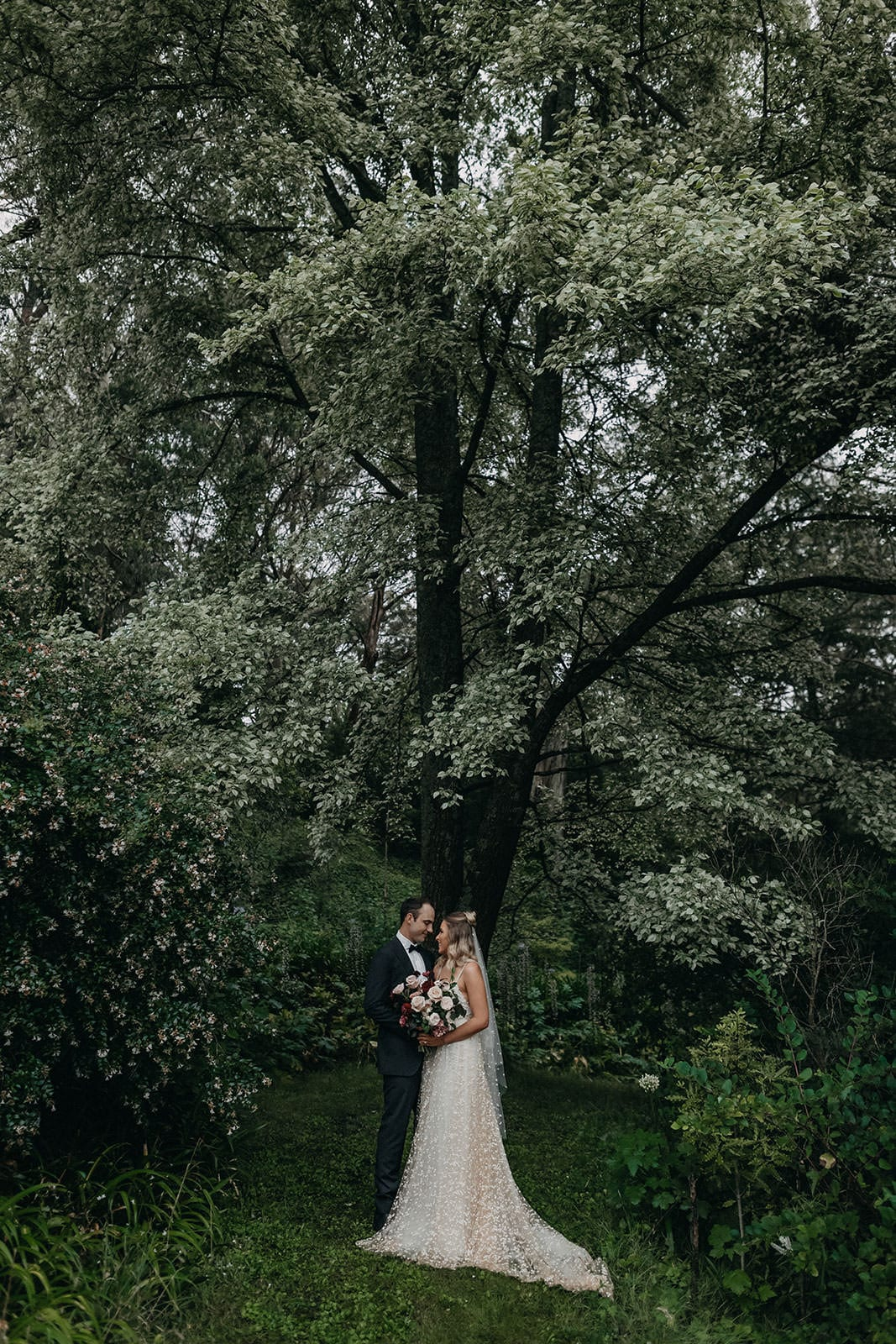 Blonde bride wearing Grace Loves Lace Menha Gown and matching veil standing with groom holding bouquet underneath tree