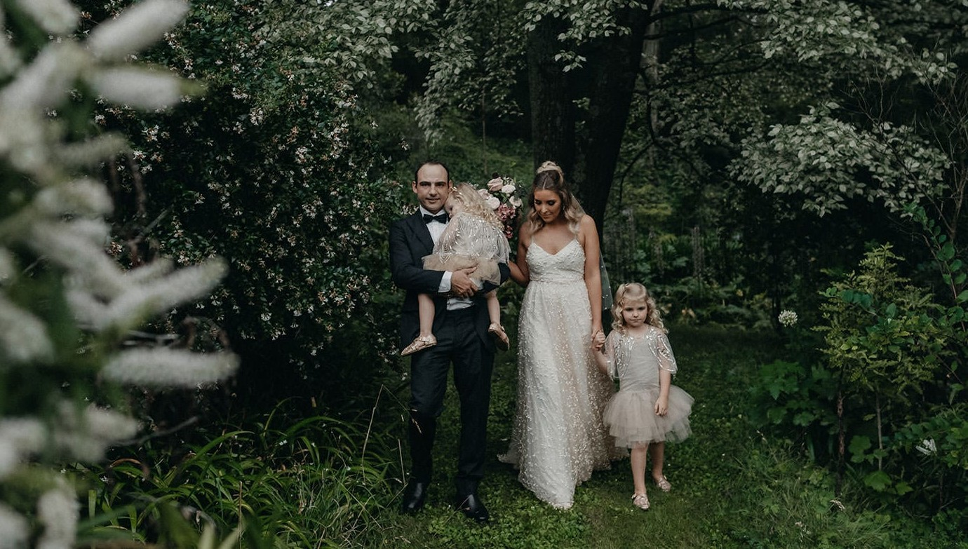 Blonde bride wearing Grace Loves Lace Menha Gown and matching veil standing with groom and two girls underneath tree